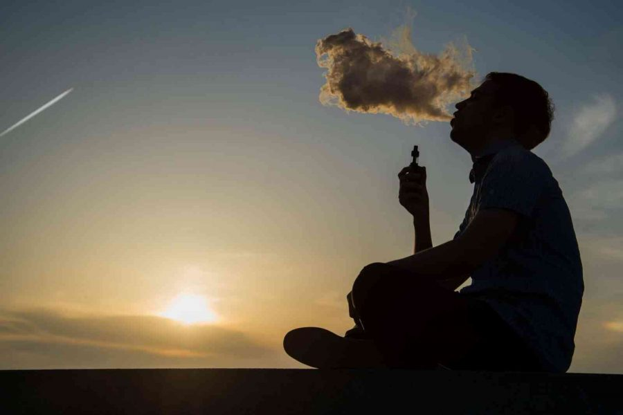 vaping young man with, produces vapor on sunset sky background at the sea coast promenade, place for text.